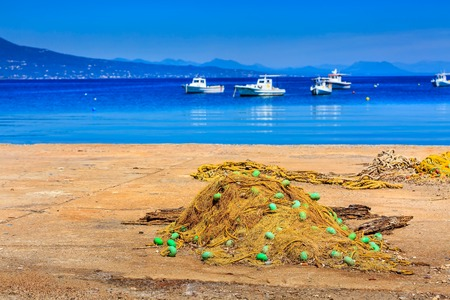 Fishing nets on the shore and boats in the sea in Messinia, Peloponnese, Greece