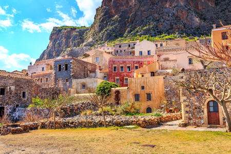 Monemvasia street panorama with old houses, trees in ancient town, Peloponnese, Greece