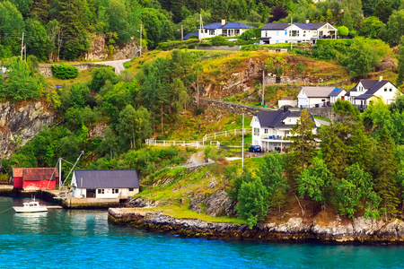 Norwegian scandinavian village landscape with jewel blue fjord water, mountains and colorful traditional houses, Norway