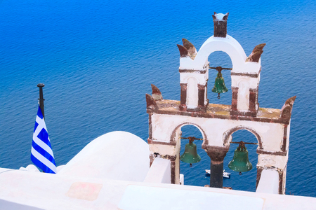Sea view, greek flag and white church bell tower, Santorini, Greece