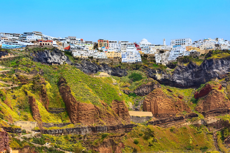 Fira or Thira panoramic view in Santorini Island with white and blue houses on high volcanic rocks in Greece