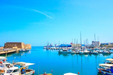 Heraklion, Greece, Crete island old harbor with fishing boats and Venetian fortress of Rocca al Mare panorama Standard-Bild
