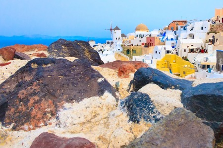 Santorini island, Greece, Oia village with windmill and colorful houses view from old stone castle