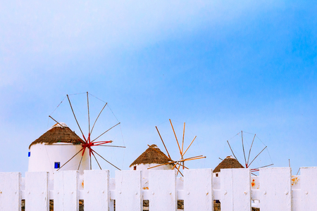 Mykonos, Greece, copy space background with greek iconic windmills and white fence in famous island in Cyclades