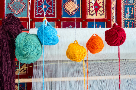 Loom for hand weaving carpet and colorful ball of yarn close-up view Standard-Bild - 123492178