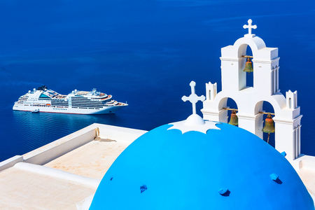Santorini, Greece iconic view of blue and white church dome and bell tower, sea and cruise ship