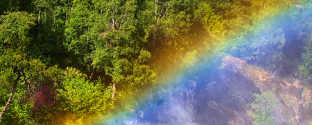 Green mountain forest through waterfall rainbow on the way to Briksdal or Briksdalsbreen glacier in Olden, Norway