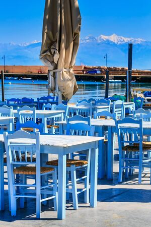 Sea view, cafe tavern tables and mountain peaks panorama in Messinia, Peloponnese, Greece