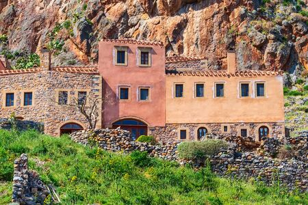 Monemvasia, Peloponnese, Greece street view with old houses in ancient town close-u and green grass