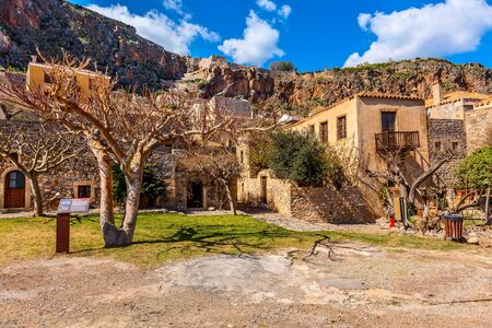 Monemvasia, Peloponnese, Greece street view with old houses and trees in ancient town