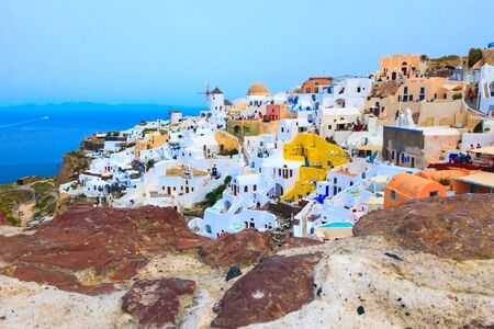 Santorini island, Greece, Oia village with windmills and colorful houses view from old stone castle