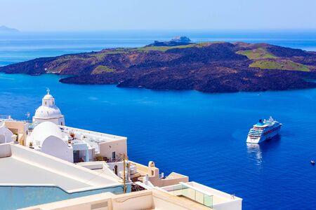Santorini, Greece iconic view of white houses, church dome, caldera, volcano island and sea panorama with cruise ship