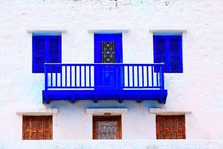 Greek traditional architecture, house with white and blue house windows, balcony close-up