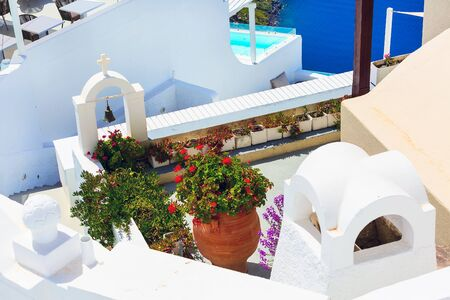 Santorini, Greece view of white bell tower, cross, flowers and blue sea Banco de Imagens