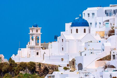 Santorini island, Greece, white houses village panoramic view with blue church dome and bell tower Banco de Imagens