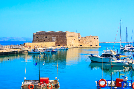 Heraklion, Greece, Crete island old harbor with fishing boats and Venetian fortress of Rocca al Mare panorama
