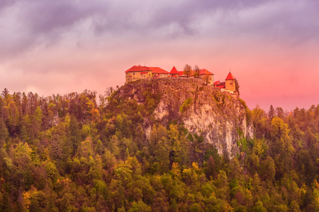 Medieval castle on rock top at Bled lake in Slovenia, autumn trees forest and colorful clouds Editorial