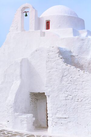 White Paraportiani Church on the island of Mykonos, Greece close-up bell tower with blue sky background