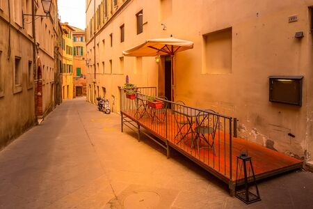 Italy landmark, Tuscany Siena medeival town, narrow street view and small tavern, scooter at sunset or sunrise 免版税图像