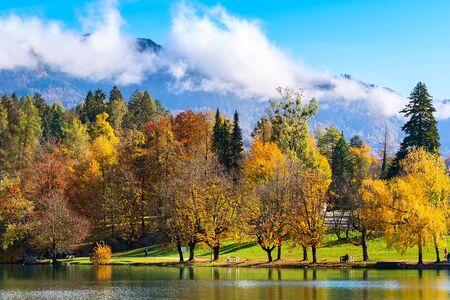 Słowenia, widok na jezioro Bled z wielobarwnymi jesiennymi drzewami i górami z chmurami