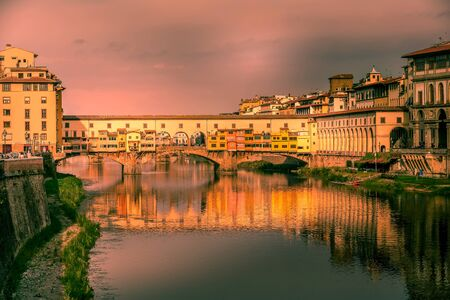Florence, Italy purple sunset view of Ponte Vecchio and reflection in the river Arno