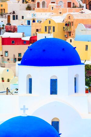 Santorini island, Greece, Oia village view with blue church dome and colorful houses