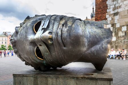 Krakow, Poland - June 18, 2019: Head sculpture Eros Bendato on Market Square by polish artist Igor Mitoraj