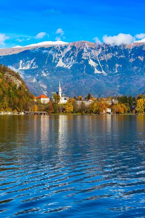 View of Lake Bled with Church, Slovenia. Autumn colorful trees and snow mountains background 写真素材