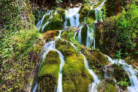 Beautiful waterfall cascade in the forest, spring nature background Banco de Imagens - 128575622