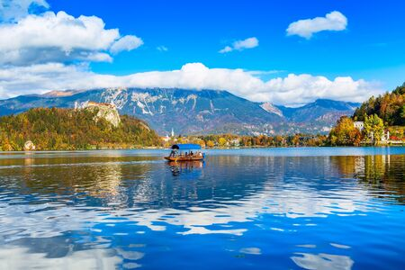 Lake Bled in Slovenia panoramic view with castle, boat and autumn trees in Julian Alps mountains