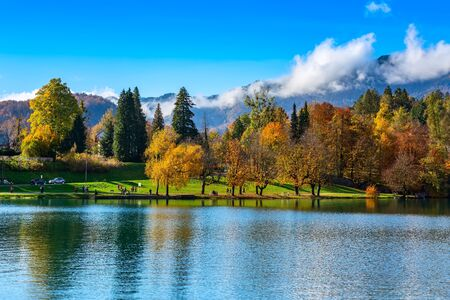 Slovenia, lake Bled view with multi colored autumn trees and mountains with clouds 写真素材
