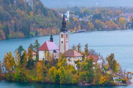 Lake Bled with Church of the Assumption of Maria, Slovenia and autumn colorful trees background Imagens - 129726131
