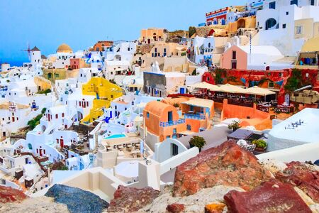 Santorini island, Greece, Oia village panorama with windmill and colorful houses view from old stone castle