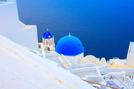 Santorini, Greece, Oia town village panorama with sea and iconic view of blue and white church dome