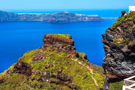 Santorini, Greece panorama with Skaros rock, big volcanic stone and caldera sea, flowers and volcano island background Фото со стока