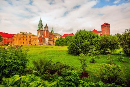 Krakow, Poland, Wawel Royal Castle colorful postcard view against flowers and green trees in the garden