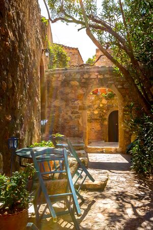Monemvasia, Peloponnese, Greece street view with old houses and cafe in ancient town Banco de Imagens