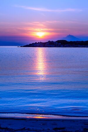Silhouette of Holy Mount Athos, Greece at colorful sunrise or sunset and sea panorama