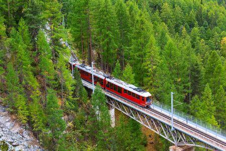 Zermatt, Switzerland. Gornergrat red tourist train close-up on the bridge in Swiss Alps