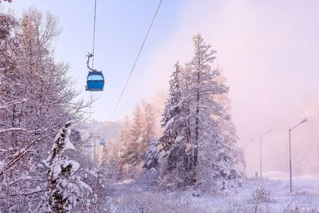 Bansko, Bulgaria pink sunset or sunrise winter resort view with ski slope in the forest, cable car cabins and mountain peaks