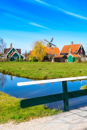 Zaanse Schans, Holland, Netherlnds traditional village houses and bridge, windmill against blue sky Stockfoto