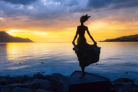 Montreux, Switzerland metal figure of woman looking sunset at promenade of Geneva Lake, colorful blue and yellow background Banco de Imagens