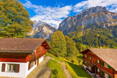 Grindelwald, Switzerland aerial village view and autumn Swiss Alps mountains panorama landscape, wooden chalets on green fields and high peaks in background, Bernese Oberland, Europe