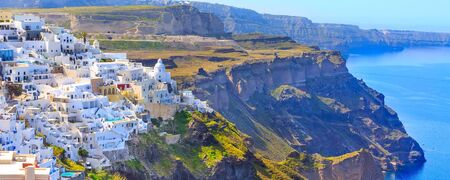 Santorini town Fira, Greece banner panorama with white houses and high volcanic rocks and blue sea 스톡 콘텐츠
