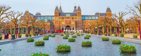Amsterdam, Netherlands - March 31, 2016: Water and colorful tulip flowers, Rijksmuseum and people in front of writing, I amsterdam, Museumplein, Holland Editorial