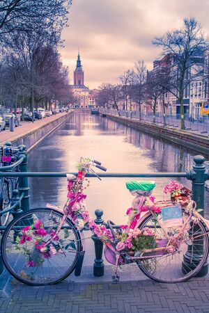 Dutch bike decorated with flowers next to a canal in The Hague, Netherlands and canal view