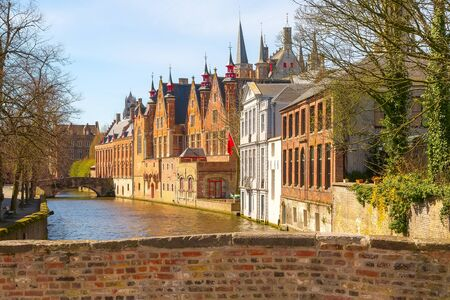 Bruges, Belgium historic medieval brick houses with towers street view along Groene Rei canal