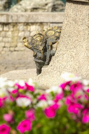Dwarf gnome with sunflower near flower bed, sculpture, symbol of Wroclaw, Poland Banco de Imagens