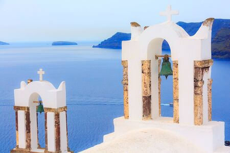 Santorini, Greece iconic view of white church cross and bell tower, blue sea background