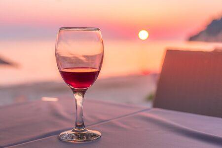 Verre de vin romantique. Coucher de soleil sur la plage reflété dans le vin rouge, concept de vacances d'été